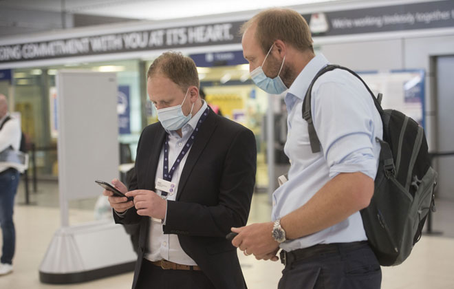 Two men wearing face masks checking a mobile phone