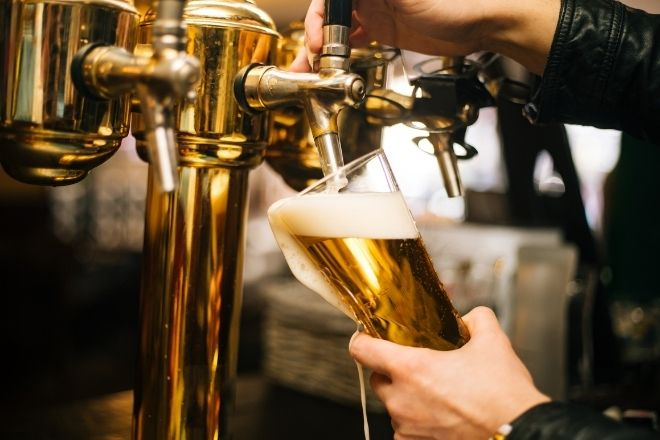 a person pouring a pint of beer in a pub