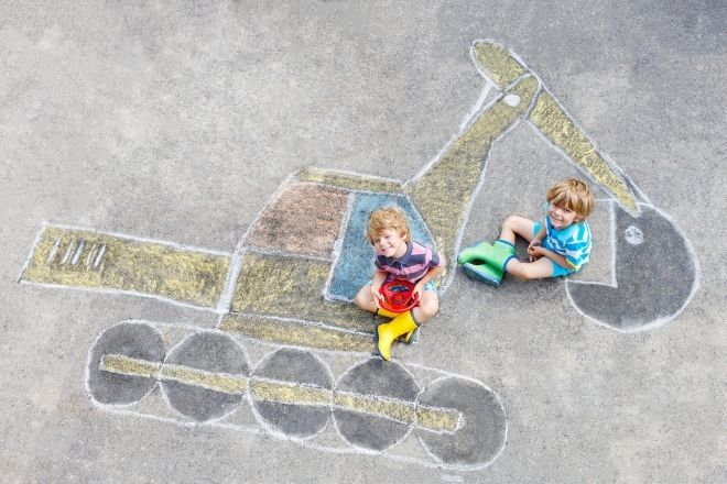 two children sat on a chalk drawing of a digger