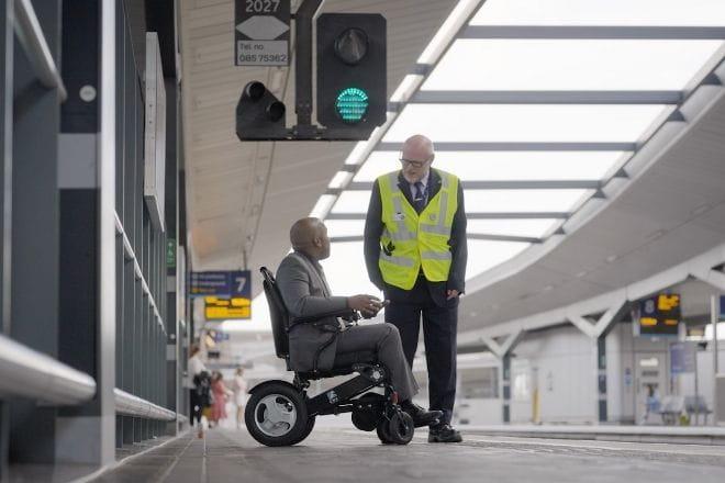 Southeastern colleague talking to a man in a wheelchair on a train platform