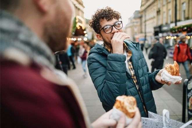 a person covering his mouth while eating some food