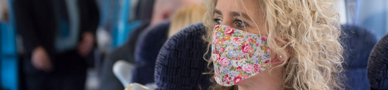 a woman on a train wearing a mask