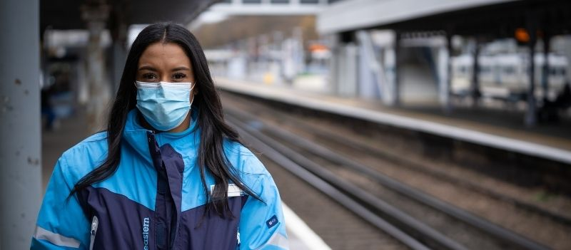 a woman with a mask standing on a train platform