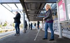 a woman with blind stick waiting on a platform