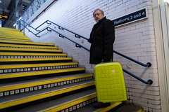 a man carrying luggage up some stairs