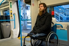 a man in a wheelchair on board a train