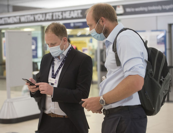 Two smartly dressed men wearing facemasks checking a mobile phone
