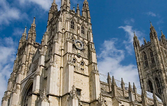 a large tall tower with a clock on the side of Canterbury Cathedral